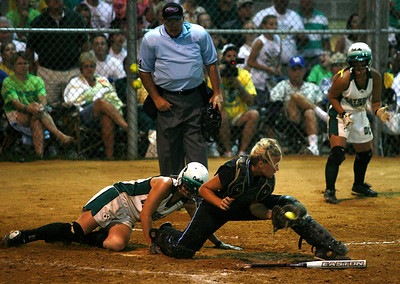 Owensboro Catholic baserunner Carly Kaelin slides across home plate while Mercy catcher Kellie Quarles snags a throw from the field, attempting the forceout during the KHSAA Fast Pitch Softball Championship Game Saturday night in Owensboro. Kaelin was ruled safe on the play. Owensboro Catholic won the game 12-2. (Photo by Bryan Leazenby, special to the Courier-Journal) June 6, 2009.