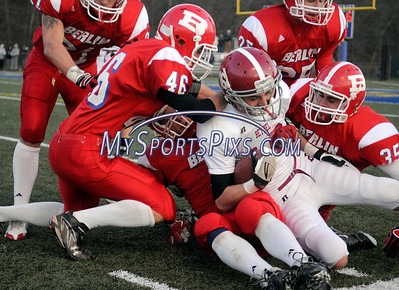 12/6/2009 Mike Orazzi | Staff Bethel's William Eisele (16) gets brought down by a host of Berlin Redcoats during a 46-6 Berlin win in the Class M football playoff on Sunday at Municipal Stadium in Waterbury.
