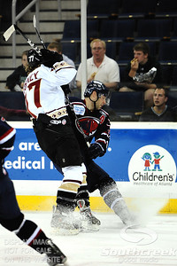 Gwinnett forward Michael Forney (#77) battles for the puck while sending ice flying in ECHL Hockey action between South Carolina and Gwinnett.  South Carolina defeated Gwinnett 5-2 in the game at The Arena at Gwinnett in Duluth, GA.
