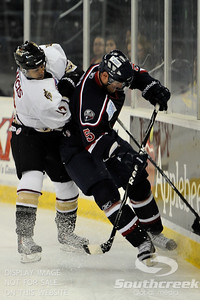 Gwinnett forward Matt Francis (#19) tries to push South Carolina defenseman Nate Kiser (#5) into the wall in ECHL Hockey action between South Carolina and Gwinnett.  South Carolina defeated Gwinnett 5-2 in the game at The Arena at Gwinnett in Duluth, GA.