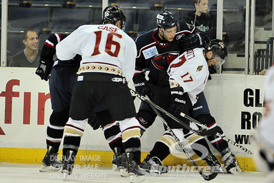 Gwinnett defenseman Matt Case (#16) and right wing Derek Nesbitt (#17) attempt to keep the puck away from the South Carolina players in ECHL Hockey action between South Carolina and Gwinnett.  South Carolina defeated Gwinnett 5-2 in the game at The Arena at Gwinnett in Duluth, GA.