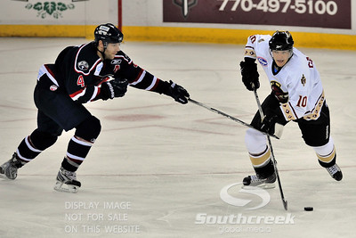 South Carolina defenseman Bryan Schmidt (#4) tries to stop Gwinnett forward Ryan Garbutt (#10) with his stick in ECHL Hockey action between South Carolina and Gwinnett.  South Carolina defeated Gwinnett 5-2 in the game at The Arena at Gwinnett in Duluth, GA.