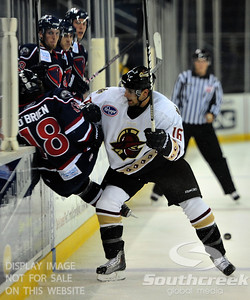 Gwinnett defenseman Matt Case (#16) knocks South Carolina center Pierre-Luc O'Brien (#18) into the wall in front of the South Carolina bench in ECHL Hockey action between South Carolina and Gwinnett.  South Carolina defeated Gwinnett 5-2 in the game at The Arena at Gwinnett in Duluth, GA.