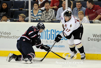 South Carolina center Pierre-Luc O'Brien (#18) goes to his knees while going for the puck again Gwinnett right wing Derek Nesbitt (#17) in ECHL Hockey action between South Carolina and Gwinnett.  South Carolina defeated Gwinnett 5-2 in the game at The Arena at Gwinnett in Duluth, GA.