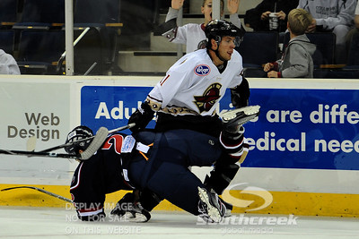 Gwinnett forward Dan Kissel (#11) knocks South Carolina defenseman Josh Godfrey (#2) to the ice in ECHL Hockey action between South Carolina and Gwinnett.  South Carolina defeated Gwinnett 5-2 in the game at The Arena at Gwinnett in Duluth, GA.