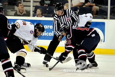 South Carolina center Pierre-Luc O'Brien (#18) and Gwinnett forward Tim Miller (#18) fight for the puck on a face off in ECHL Hockey action between South Carolina and Gwinnett.  South Carolina defeated Gwinnett 5-2 in the game at The Arena at Gwinnett in Duluth, GA.