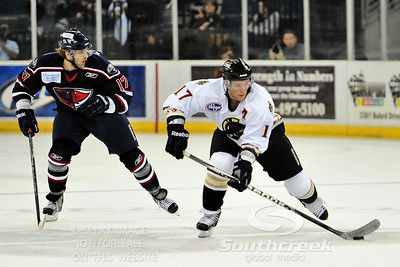 Gwinnett right wing Derek Nesbitt (#17) attempts to get away from South Carolina forward Nikita Kashirsky (#17) in ECHL Hockey action between South Carolina and Gwinnett.  South Carolina defeated Gwinnett 5-2 in the game at The Arena at Gwinnett in Duluth, GA.