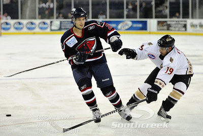 South Carolina defenseman Josh Godfrey (#2) fends off Gwinnett forward Matt Francis (#19) in ECHL Hockey action between South Carolina and Gwinnett.  South Carolina defeated Gwinnett 5-2 in the game at The Arena at Gwinnett in Duluth, GA.