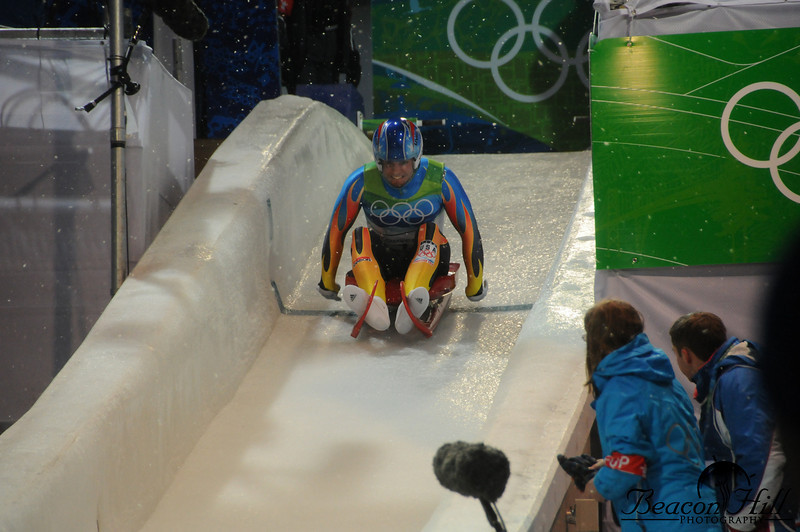 """An American athlete pushes off at the start of the luge run. After an unfortunate accident which killed a Georgian luger, the men's start was moved to this location which was originally the women's starting position. The women, in turn, were moved even lower on the course. Despite the lower starting elevation, the final speeds of the athletes ended up being very close to the speeds during training from the original starting position. In the lower right you see a blue coated volunteer worker wearing a red armband. This  armband, with the letters """"FOP"""" allows the volunteer access to the Field of Play. Other volunteers without this armband would not be permitted track side."""