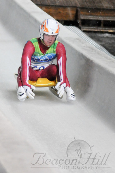 A luge athlete finishes his run and is braking by lifting the front of the sled. The perspective is deceiving in this photograph -- the luger is actually travelling up hill at this point in the track, which is after the finish line but before the camera- and crowd-laden take out area where the sleds and athletes leave the course.
