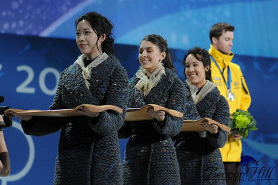 The Australian mogul silver medalist is visibile behind the medal and flower tray girls, a fixture of every Olympics. Apparently the Vancouver Organizing Committee (VANOC) will be auctioning these very trays after the Olympics.
