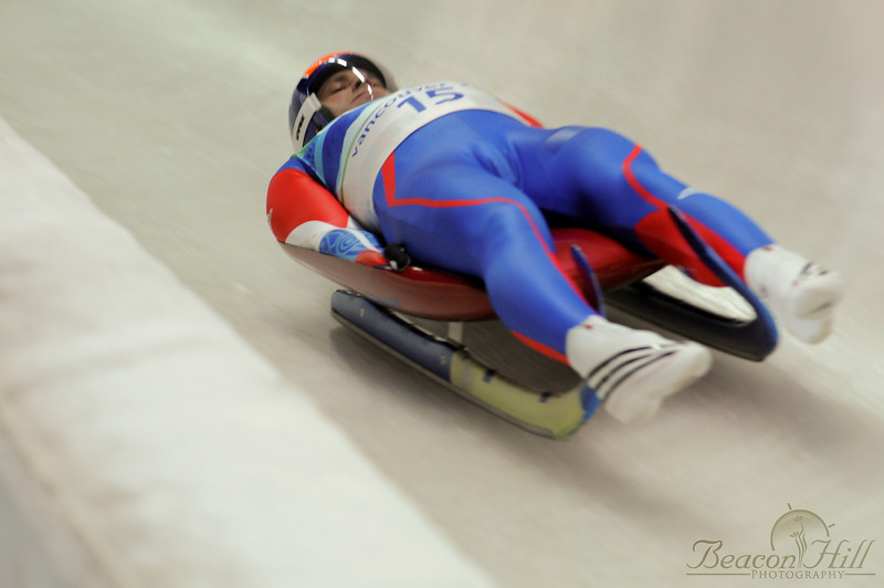 """I freely admit I had no idea what country this athlete represents, but this photograph illustrates very well the position the lugers are in during their runs. Steering is accomplished primarily by pushing on the """"horns"""" in the front with the ankles."""