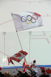 A Canadian fan waves a combination Olympic/Canadian flag. He is wearing a helmet with a flashing light which he turned on whenever a goal was scored.