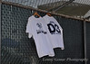 "The baseball team remember their <a href=""http://www.lennygemar.com/Family/KyrstinRaeGemar/"">three lost comrades</a> from DSU softball, who tragically died on November 1st, 2009.  Because the wind was blowing, the shirts might be hard to read.  The first shirt had a picture of Buster, the Blue Hawk mascot, and says ""Birds of a feather flock together.""  The second shirt  memorializes the girls: ""A.K.A. - Ashley, Kyrstin, Afton. D3, R.I.P. Lady Hawks."" D3 stands for Dickinson Three, what the girls were initially referred to after their disappearance."