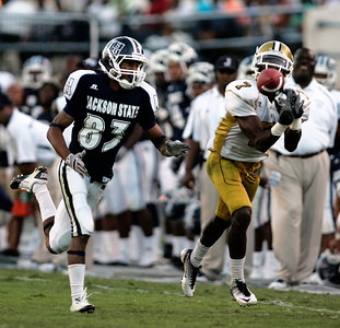 Jackson State receiver Rico Richardson attempts to stop an Alabama St. defender from intercepting a pass.