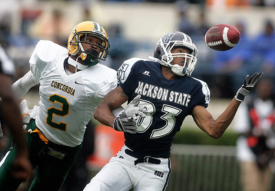 Jackson State receiver Rico Richardson attempts to gain control  of a pass as a Concordia defender looks on.