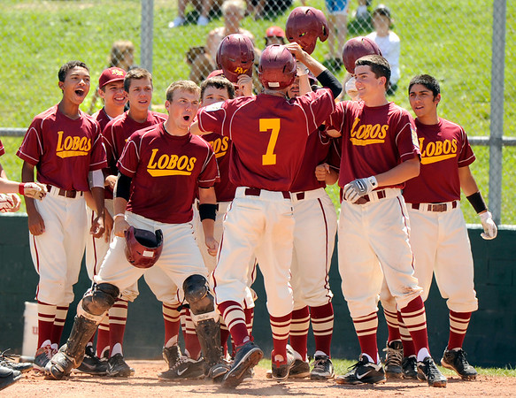 """Rocky Mountain's Cale O'Donnell, No. 7, gets congratulated by his teammates after hitting a 3-run home run on Sunday, July 31, during the Colorado State Legion A Championship game against Fairview at Fairview High School in Boulder. Rocky Mountain Lobos defeated Fairview 12-6. For more photos of the game go to  <a href=""""http://www.dailycamera.com"""">http://www.dailycamera.com</a><br /> Jeremy Papasso/ Camera"""