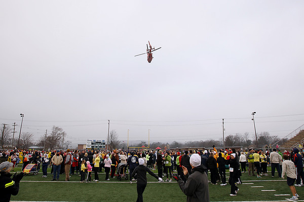 Record-Eagle/Keith King<br /> A helicopter from the United States Coast Guard Air Station Traverse City flies overhead at the conclusion of the National Anthem Thursday, November 24, 2011 prior to the start of the fourth annual Traverse City Turkey Trot at Thirlby Field.