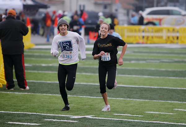 Record-Eagle/Keith King<br /> Brad Clark, left, and Kaylee Vandommelen sprint toward the finish line at Thirlby Field Thursday, November 24, 2011 during the fourth annual Traverse City Turkey Trot.