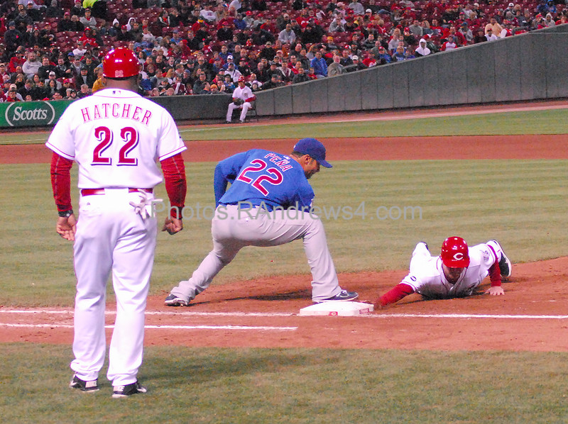 First base coach Billy Hatcher looks on while Drew Stubbs dives back to first base before Carlos Pena can tag him with the pick off attempt from Carlos Zambrano.