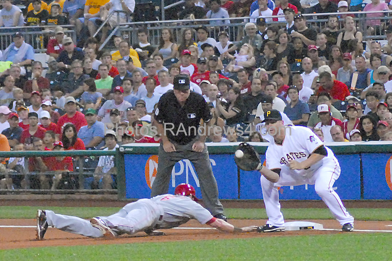 Pirate first baseman Lyle Overbay waits for the throw as the pitcher attempts to pick Cincinnati Reds left fielder Drew Stubbs off first base under the watchful eyes of first base umpire Tony Randazzo.