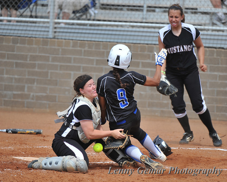 Morningside's catcher, who has reached out to block the plate, collides with #9 Patricia Banda.  The ball is dropped, and Banda scores CSUSM's 3rd run.
