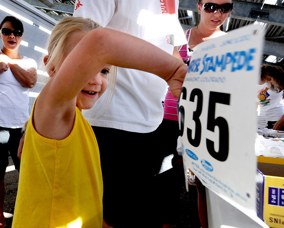 "Rylee Soutiea, 4, collects her race number for the Sunrise Stampede with her parents on Saturday.<br /> For more photos and a video of the race, go to  <a href=""http://www.dailycamera.com"">http://www.dailycamera.com</a> or timescall.com.<br /> Cliff Grassmick / June 9, 2012"