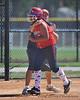 Coach congratulates Tricia Niu as she rounds 3rd base.