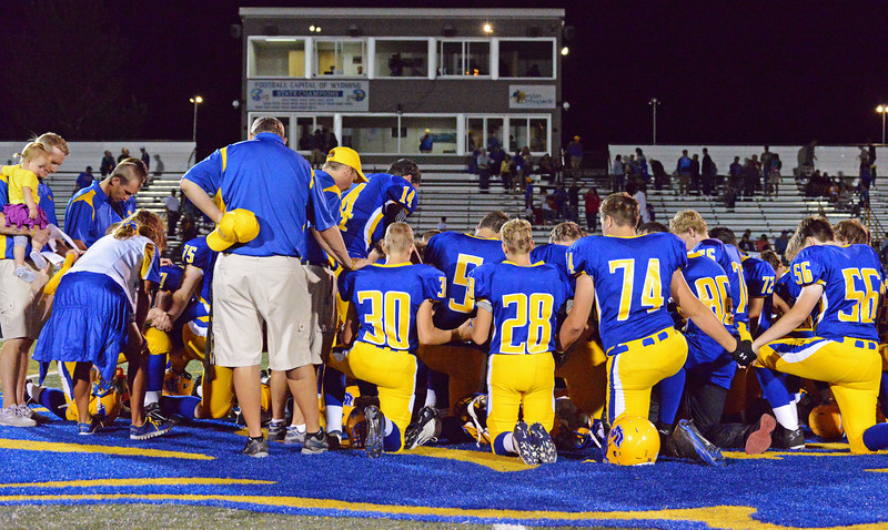 Broncs captian Daniel Sessions leads the team in a prayer after their 26-10 win Friday night in Sheridan.