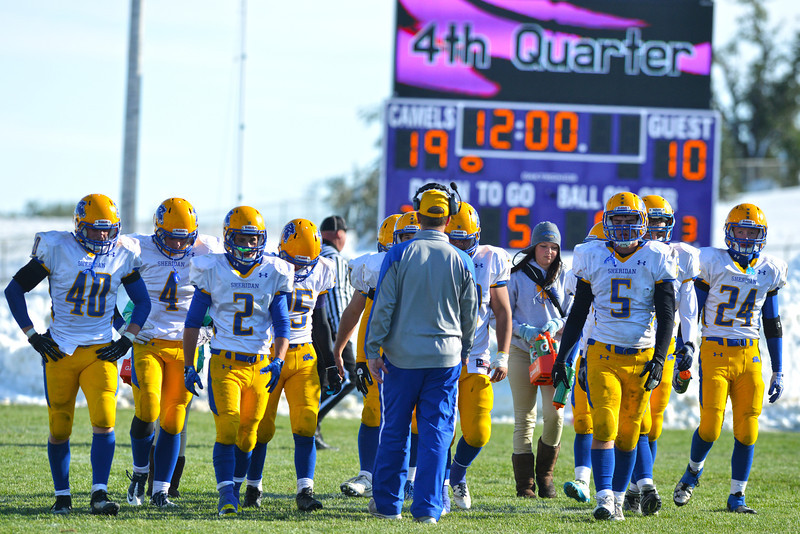 Sheridan assistant coach D.J. Dearcorn walks with his defense to the other end of the field as the fourth quarter began Saturday. The Broncs would give up a touchdown on the first play of the final period and not recover in a 39-10 loss, their first of the year. (Brad Estes/The Sheridan Press)