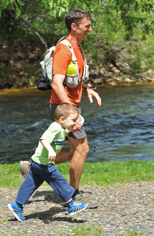 Missouri man Kyle Gibbs runs towards the finish line after running the 100 Mile race in the Bighorn Mountain Wild and Scenic Trail Run Saturday at Scott Bicentennial Park in Dayton. Gibbs walked across the finish line with his son Karson, 2, who joined him in the park.