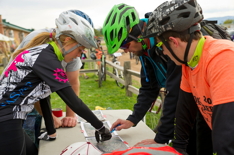 Casper bicyclists from left; Chloe Sale, Leif Hohansson, and Logan Santistevan huddle around a map of the route that they will be taking during the Biketober Fest race at the Sheridan County Fairgrounds on Saturday.