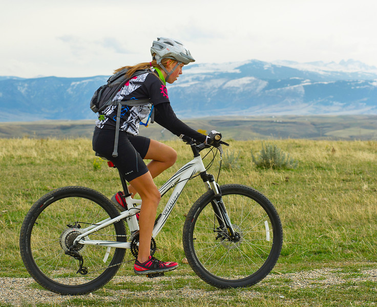Chloe Sales of Casper peddles along Soldier Ridge Trail with a view of the Bighorn Mountains in the 25-mile mountain bike race during Saturday's Biketober Fest. The fundraising event was to benefit the Sheridan County Land Trust which made projects like the Soldier Ridge Trail possible.