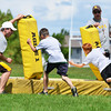 Campers dive during tackling drills Monday afternoon on the Sheridan High School practice field.