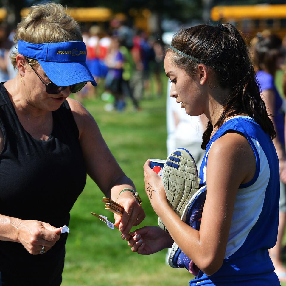 Sheridan High School principal Dirlene Wheeler takes Xiomara Robinson's name tag to record her finish after the varsity girls race Saturday.