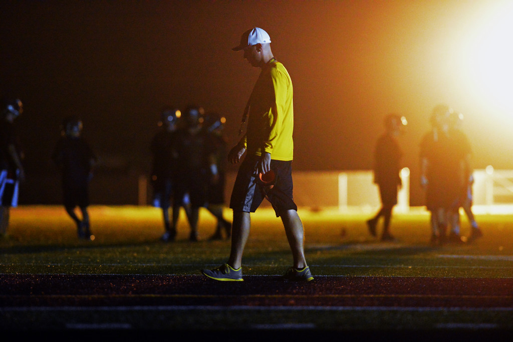 Second-year head coach Michael McGuire walks in the end zone while his team runs through warm-up lines during Big Horn Rams football practice early Monday morning. (Brad Estes/The Sheridan Press)