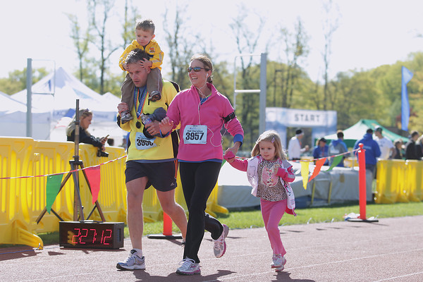 Record-Eagle/Keith King<br /> Kevin and Sharon Holt, of DeWitt, run with their children Bryce Holt, left, 2, and Adolie Holt, 4, Saturday, May 25, 2013 as they near the finish line during the 31st annual Bayshore running races.