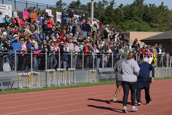 Record-Eagle/Keith King<br /> Spectators look on as runners near the finish line at Traverse City Central High School Saturday, May 25, 2013 during the 31st annual Bayshore running races.
