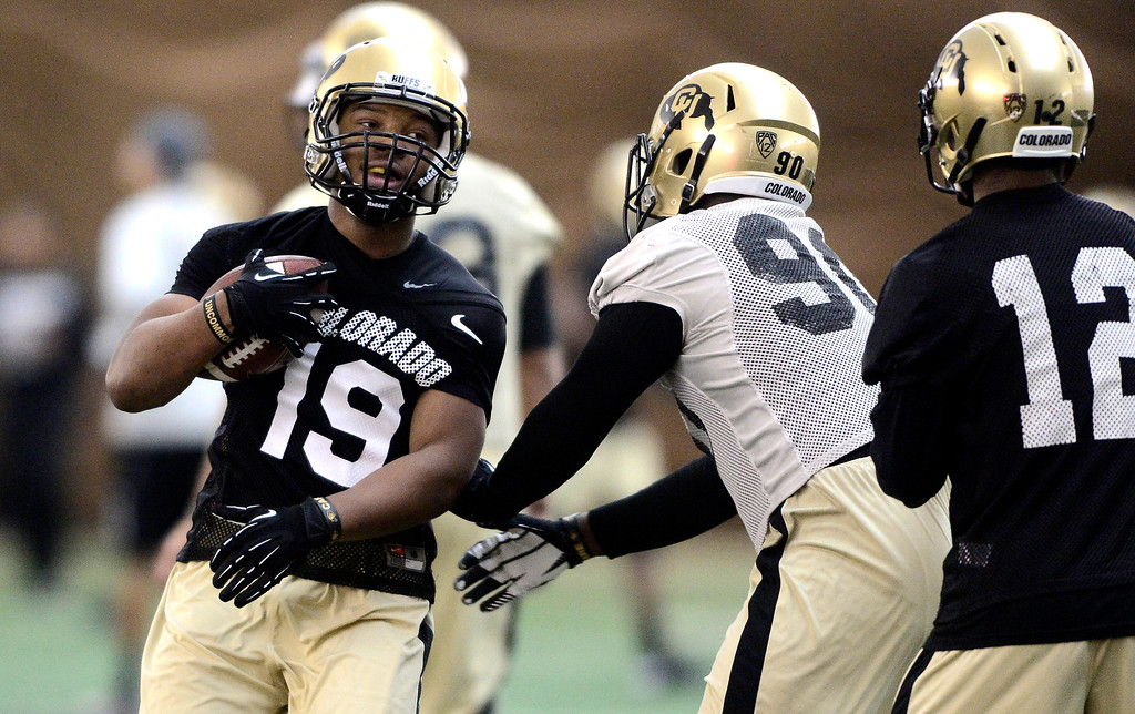 . University of Colorado\'s tailback MIchael Adkins (19) finishes a run in the practice bubble on CU\'s Boulder campus on Friday during the football team\'s first spring practice. March 7, 2014. For more photos go to www.buffzone.com. Photo by Paul Aiken / The Boulder Daily Camera