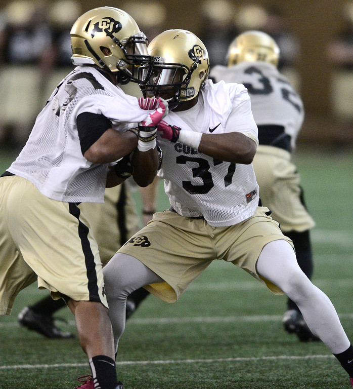. University of Colorado\'s Derek McCartney (95) battles Woodson Greer (3&) during a drill in the practice bubble on CU\'s Boulder campus on Friday during the football team\'s first spring practice. March 7, 2014. For more photos go to www.buffzone.com. Photo by Paul Aiken / The Boulder Daily Camera
