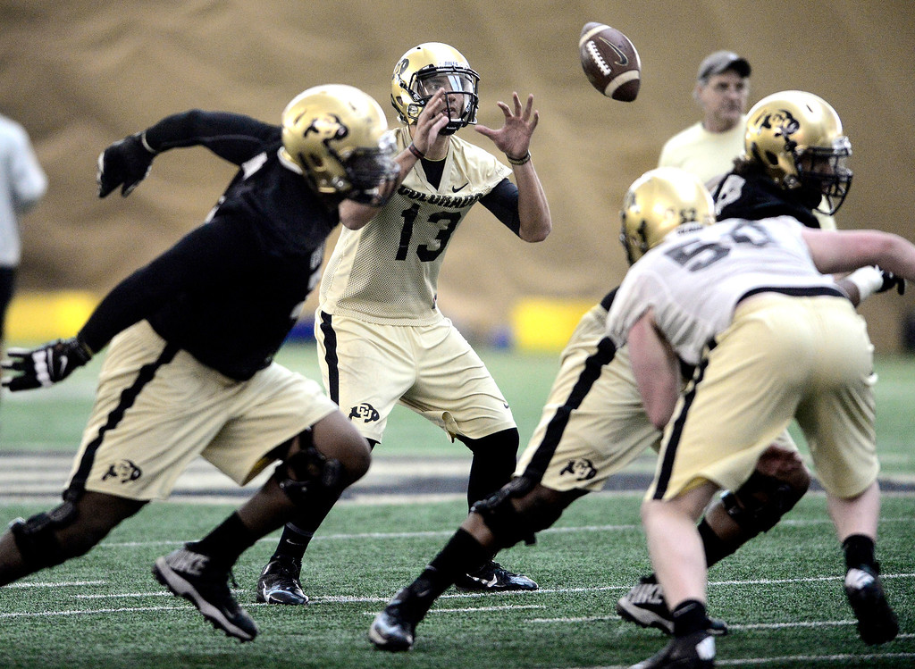 . University of Colorado\'s quarterback Sefo Liufau (13) takes a snap in the practice bubble on CU\'s Boulder campus on Friday during the football team\'s first spring practice. March 7, 2014. For more photos go to www.buffzone.com. Photo by Paul Aiken / The Boulder Daily Camera