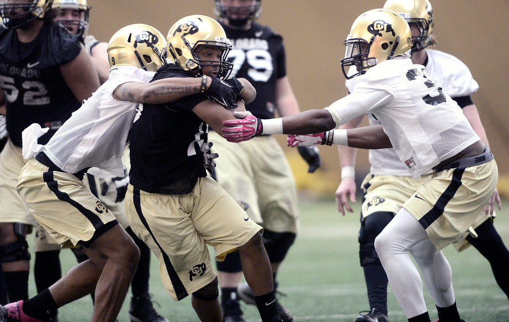 . University of Colorado\'s tailback MIchael Adkins (19) tries to break free from defensive back Tedric Thompson (9) in the practice bubble on CU\'s Boulder campus on Friday during the football team\'s first spring practice. March 7, 2014. For more photos go to www.buffzone.com. Photo by Paul Aiken / The Boulder Daily Camera