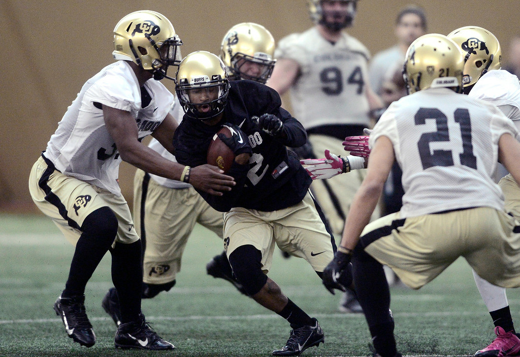 . University of Colorado\'s Keenan Canty (12) tries to run past Kenneth Olugbode (31) in the practice bubble on CU\'s Boulder campus on Friday during the football team\'s first spring practice. March 7, 2014. For more photos go to www.buffzone.com. Photo by Paul Aiken / The Boulder Daily Camera