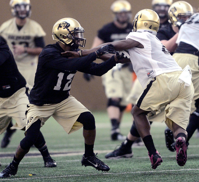 . University of Colorado\'s Keenan Canty (12) blocks Chidobe Awauzie (4)  in the practice bubble on CU\'s Boulder campus on Friday during the football team\'s first spring practice. March 7, 2014. For more photos go to www.buffzone.com. Photo by Paul Aiken / The Boulder Daily Camera