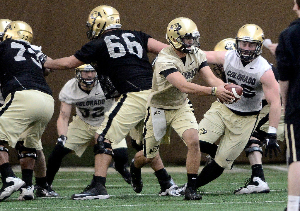 . University of Colorado\'s Jordan Gehrke (7) hands off the football in the practice bubble on CU\'s Boulder campus on Friday during the football team\'s first spring practice. March 7, 2014. For more photos go to www.buffzone.com. Photo by Paul Aiken / The Boulder Daily Camera