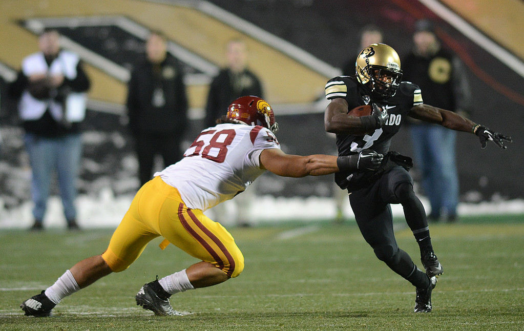 . DD Goodson of Colorado tries to get around JR Tavai of USC during the first half of the November 23, 2013 game in Boulder, Colorado.  Cliff Grassmick / November 23, 2013