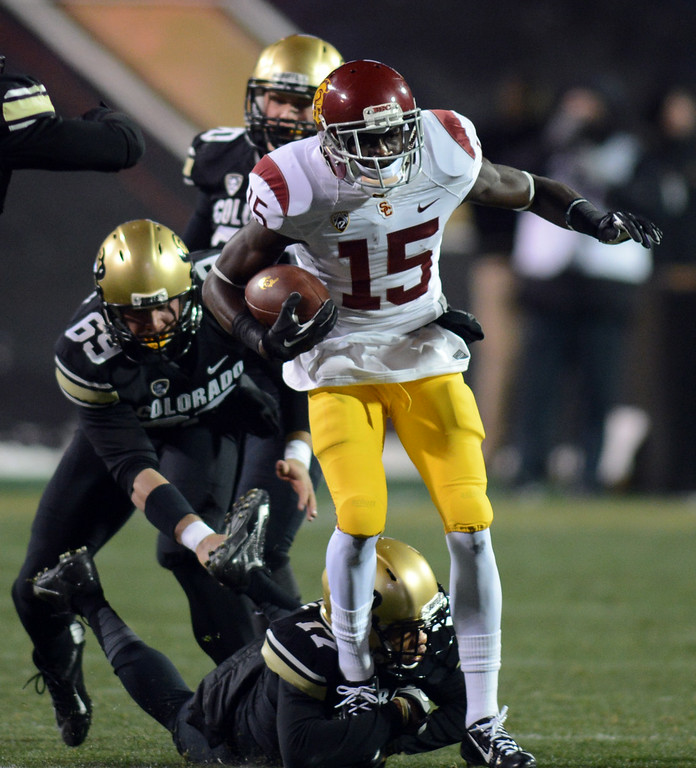 . Nelson Agholor of USC leaves a few Buffs in his wake, including Marquez Mosley (17) and Ryan Severson during a kick return in the first half of the November 23, 2013 game in Boulder, Colorado.  Cliff Grassmick / November 23, 2013