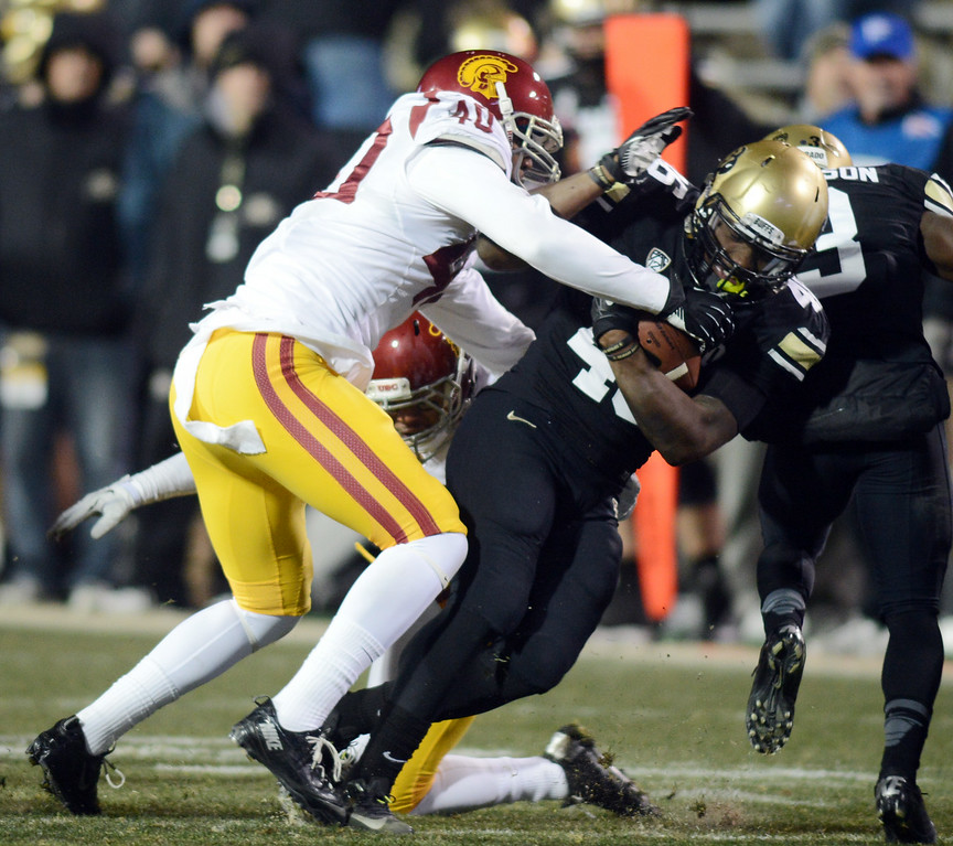 . Christian Powell of CU gets a few hard yards on Jabari Ruffin of USC during the second half of the November 23, 2013 game in Boulder, Colorado.  Cliff Grassmick / November 23, 2013