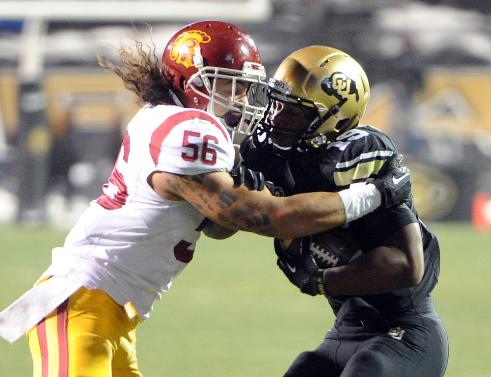 . Anthony Sarao of USC wraps up Michael Adkins II of CU during the first half of the November 23, 2013 game in Boulder, Colorado.  Cliff Grassmick / November 23, 2013