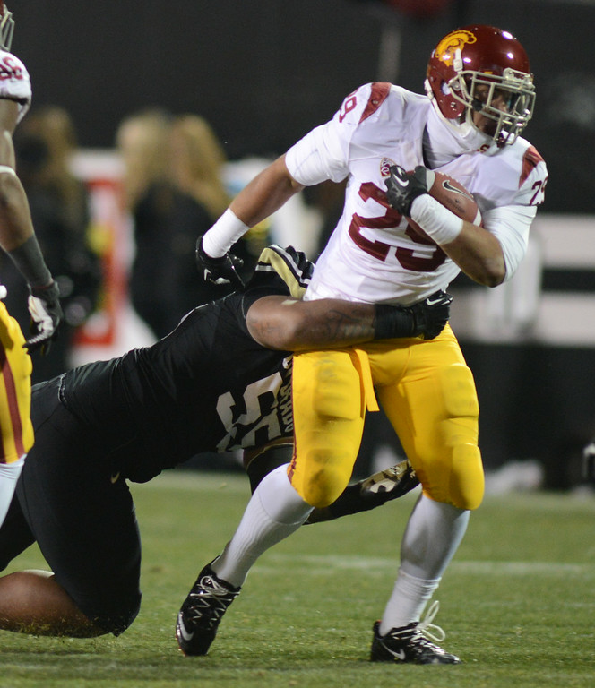 . Josh Tupou of CU tries to bring  down Ty Isaac  of USC during the first half of the November 23, 2013 game in Boulder, Colorado.  Cliff Grassmick / November 23, 2013